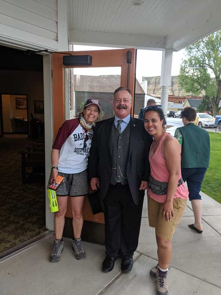 A Theodore Roosevelt impersonator dressed in a dark suit is standing in the middle of two women. All are smiling at camera. Woman on the right is wearing  a 3/4 length sleeve shirt (white body, maroon sleeves), grey shorts and a maroon baseball cap. Women on right is wearing pink sports tank tops and khaki shorts.