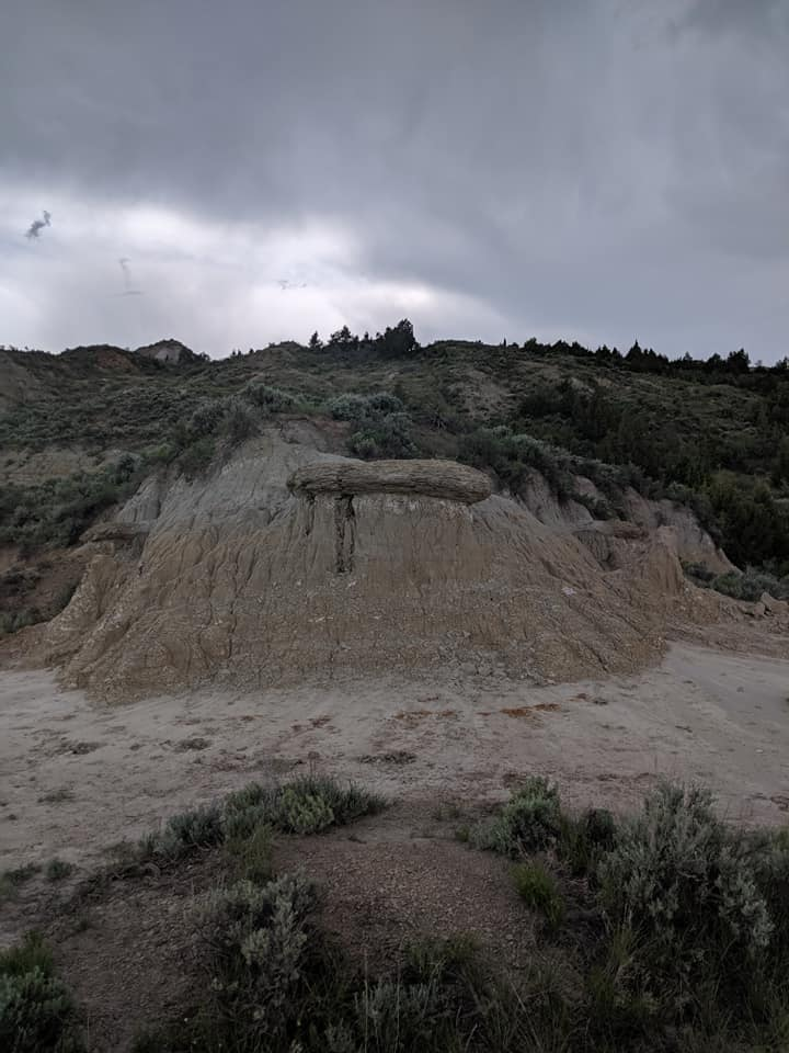 Picture taken looking up from in the Painted Canyon of Theodore Roosevelt National park. The bottom of the hill is bare brown rock. The higher on the hill the more trees and bushes there are. They sky is grey and cloudy due to an incoming storm.