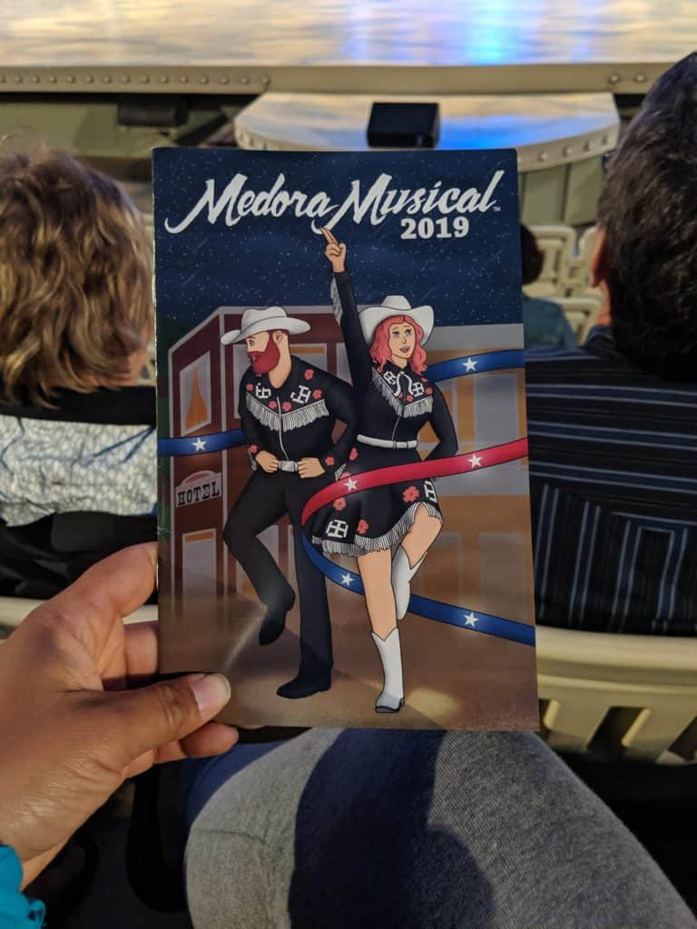 Close up of the brochure for Medora Musical 2019. It has a cartoon man and woman dressed as cowboy and cowgirl with a ribbon that is red and blue with stars on it weaving around them.